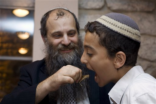 Ari Zivotofsky and one of his sons try out a locust, an ancient kosher delicacy that he has researched as part of Halachic Adventures, a side hobby Courtesy Halachic Adventures)