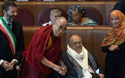 Italian movie director Bernardo Bertolucci (seated) with Rome's Mayor Ignazio Marino (left) after he received the Peace Summit Award from Tibetan spiritual leader the Dalai Lama (2nd left) and Nobel Peace Prize co-winner Tawakkol Karman (right) at the end of the 14th World Summit of Nobel Peace Laureates in Rome, December 14, 2014. (photo credit: AFP/Tiziana Fabi)