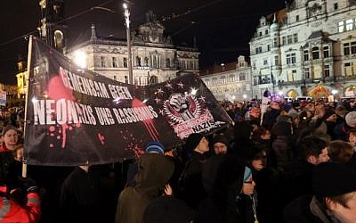 "Potestors hold up banner reading ""Together against Neo Nazis and racism"" during a demonstration under the slogan ""Dresden Nazi-free"" against the ""Patriotic Europeans Against the Islamisation of the Occident"" (PEGIDA) in Dresden, eastern Germany, on December 22, 2014. (Kay Nietfield, AFP)"