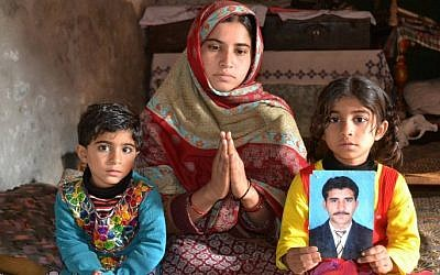 The wife of Mohammad Irfan, a Pakistani national who was sentenced to death for drug trafficking in Saudi Ariabia, gestures as she poses for a photograph with her children in Sargodha, December 2, 2014,. (photo credit: AFP/Ali TURAB)