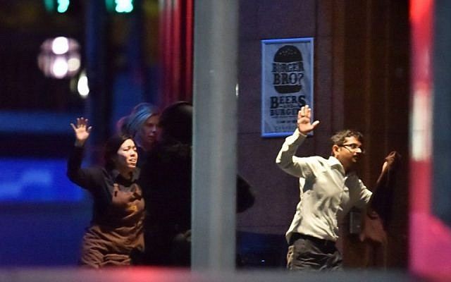 Hostages run out of a cafe in the central business district of Sydney on December 16, 2014 (photo credit: AFP/Peter PARKS)