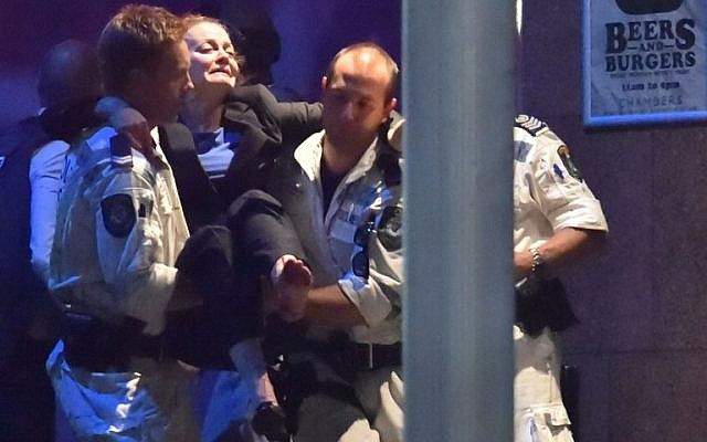 An injured hostage is carried out of a cafe in the central business district of Sydney on December 16, 2014. Police stormed the Sydney cafe where a gunman had taken hostages and displayed an Islamic flag, television footage showed early December 16 (photo credit: AFP/Peter PARKS)