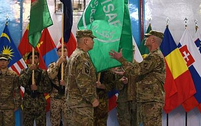 US General John Campbell (4L) lowers the flag of the NATO-led International Security Assistance Force (ISAF) during a ceremony marking the end of ISAF's combat mission in Afghanistan at ISAF headquarters in Kabul on December 28, 2014. (photo credit: AFP/ SHAH Marai)
