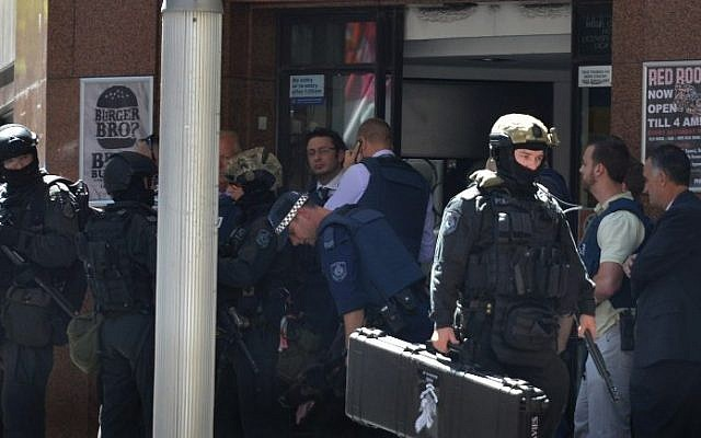 Armed police are seen outside a cafe in the central business district of Sydney on December 15, 2014. Hostages were being held inside a cafe in central Sydney on December 15 with an Islamic flag displayed against a window, according to witnesses and reports. (Photo credit: AFP/Peter Parks)