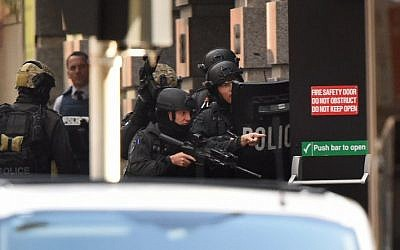 Police gesture as a hostage (unseen) escapes from an emergency exit during a hostage siege in the central business district of Sydney on December 15, 2014 (photo credit: AFP/William WEST)