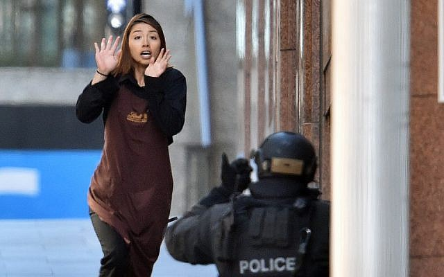 One of the hostages runs toward police from a cafe in Sydney on December 15, 2014. (photo credit: AFP/SAEED KHAN)