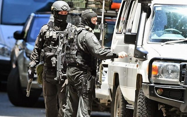 A police sniper team walk to their vehicle during a hostage siege in the central business district of Sydney on December 15, 2014. (Photo credit: AFP/William WEST)