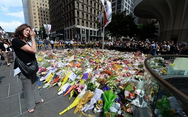 A visitor looks at a makeshift memorial near the scene of a fatal siege in the heart of Sydney's financial district on December 16, 2014. (photo credit: AFP/Peter Parks)