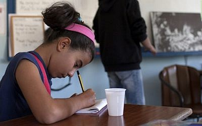 A young Syrian refugee takes notes as she listens to her English teacher during a class at the American Academy in the Cypriot capital Nicosia on November 11, 2014. (AFP/FLORIAN CHOBLET)