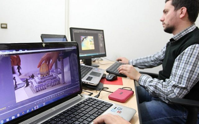 """Graphic designers work on a layout for Lebanon's """"Mahdi"""" magazine produced by the Shiite Hezbollah movement, on November 24, 2014 in the capital Beirut. (photo credit: AFP/ANWAR AMRO)"""