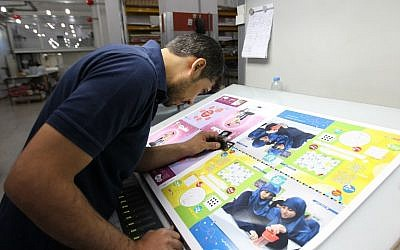 An employee checks the printing of the Mahdi magazine, produced by the Shiite Hezbollah movement, on November 24, 2014 in the Lebanon capital Beirut. (photo credit: AFP/ANWAR AMRO)