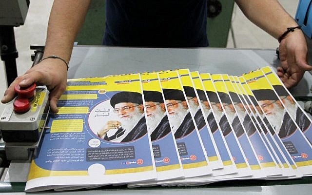 """An employee gathers copies of Lebanon's """"Mahdi"""" magazine produced by the Shiite Hezbollah movement, on November 24, 2014 at a printing house in the capital Beirut. (photo credit: AFP/ANWAR AMRO)"""