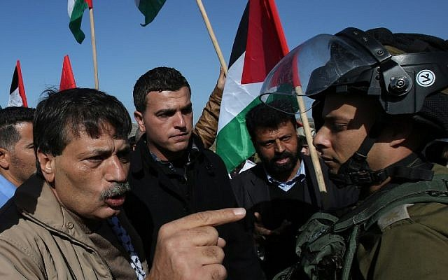 Palestinian official Ziad Abu Ein (L) argues with Israeli soldiers during a demonstration in the West Bank on Wednesday, December 10, 2014 (photo credit: AFP/ABBAS MOMANI)