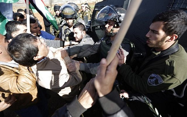 A border policeman grabs Palestinian official Ziad Abu Ein (L) during a demonstration in the West Bank on Wednesday, December 10, 2014 (photo credit: AFP/ABBAS MOMANI)