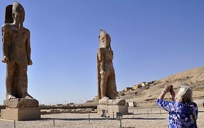 A tourist takes a picture of two colossal statues of Pharaoh Amenhotep III in Egypt's famed temple city of Luxor, December 14, 2014. (photo credit: AFP/Radwan Abu Elmagd)