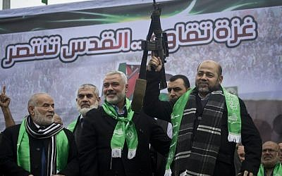 Gaza Hamas leaders Ismail Haniya, center, and Mousa Abu Marzouq, right, brandish a weapon as they greet supporters during a parade marking the 27th anniversary of the Islamist movement's creation on December 14, 2014 in Gaza City. (photo credit: AFP/MAHMUD HAMS)