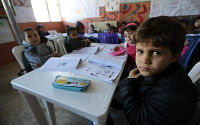 Syrian refugee children attend a class at a school for Syrian refugees in the Lebanese village of Qaraoun, in the west of the Bekaa Valley on December 16, 2014.  (photo credit: AFP PHOTO/JOSEPH EID)