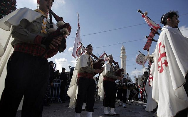 Palestinian Christian scouts perform at Manger Square outside the Church of the Nativity as Christians gather for Christmas celebrations in the West Bank city of Bethlehem, on December 24, 2014. (photo credit: AFP PHOTO/AHMAD GHARABLI)
