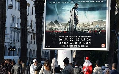 "A man dressed as Santa Claus stands next to a billboard for the Hollywood biblical epic movie ""Exodus: Gods and Kings"" displayed in the Moroccan capital Rabat on December 26, 2014. photo credit: AFP/FADEL SENNA)"