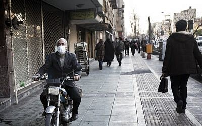 An Iranian man wearing a mask to protect himself from pollution rides his motorcycle on the pavement in downtown Tehran on December 30, 2014 (Photo credit: Behrouz Mehri/AFP)