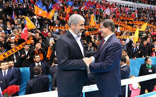 A handout made available by the Turkish Prime Minister's Press office on December 27, 2014, shows senior Hamas leader Khaled Mashaal (L) shaking hands with Turkish Prime Minister Ahmet Davutoglu. (photo credit: AFP PHOTO / HO / PM OFFICE / HAKAN GOKTEPE)