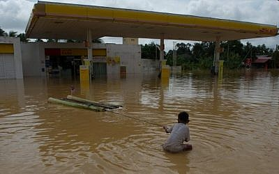 A boy plays in floodwaters near a petrol station in Pengkalan Chepa, near Kota Bharu on December 26, 2014. (Photo credit: AFP)