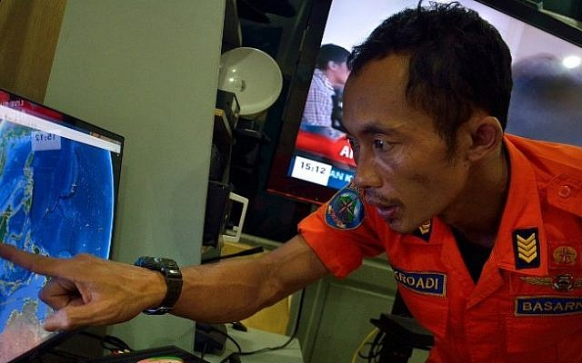 An official from Indonesia's national search and rescue agency in Medan, North Sumatra points at his computer screen to the position where AirAsia flight QZ8501 went missing off the waters of Indonesia on December 28, 2014. (Photo credit: AFP/ Sutanta ADITYA)