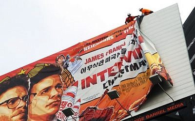 "Workers remove the poster for ""The Interview"" from a billboard in Hollywood, California, December 18, 2014 a day after Sony announced it had no choice but to cancel the movie's Christmas release and pull it from theaters due to a credible threat. (Photo credit: AFP/ VERONIQUE DUPON)"