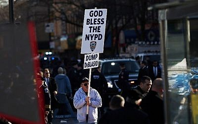 An anti-Mayor Bill de Blasio protester holds up a sign outside of Christ Tabernacle Church for the funeral of slain New York City Police Officer Rafael Ramos, one of two officers murdered while sitting in their patrol car in an ambush in Brooklyn last Saturday afternoon, on December 27, 2014 in New York City (photo credit: Spencer Platt/Getty Images/AFP)