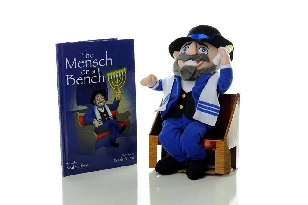 Mensch on a Bench next to the accompanying book, 'Moshe the Mensch.' (courtesy)