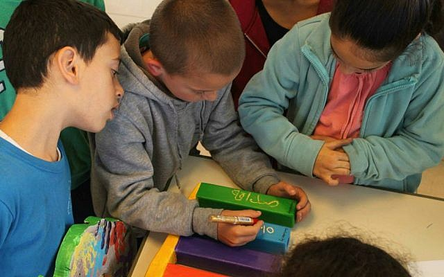 Students at the Max Rayne Hand in Hand School decorate their Hanukkah menorah with the school;s founding values in Hebrew and Arabic. (Courtesy of Hand in Hand)