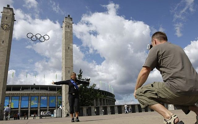 Tourists photograph themselves in front of the Berlin 1936 Olympic Stadium, its twin towers and Olympic symbol still soaring high (photo credit: AP Photo/David J. Phillip)