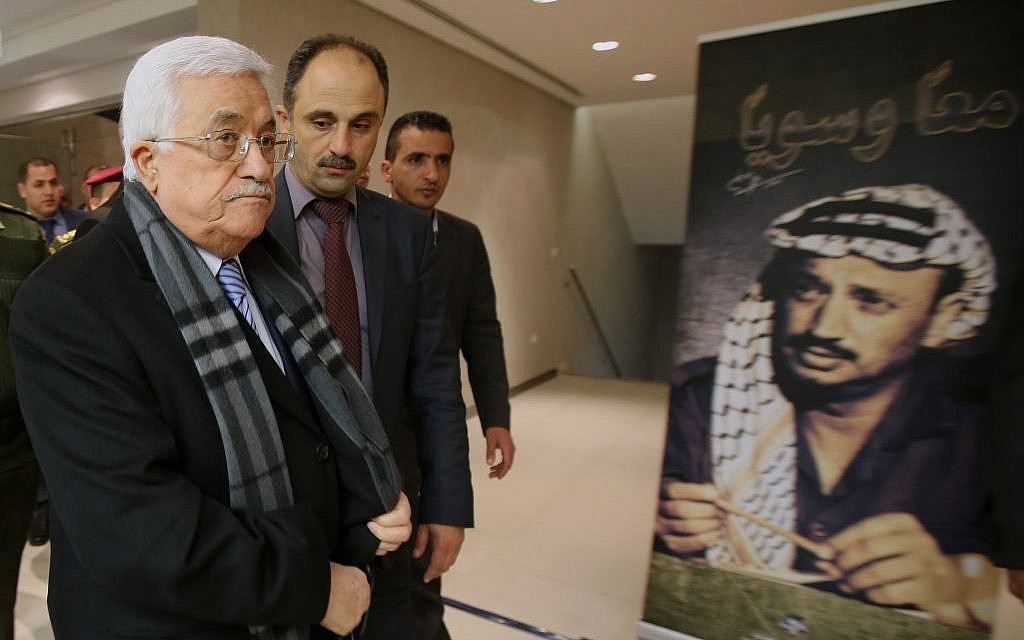 Palestinian President Mahmoud Abbas, left, arrives for the opening of a museum for late Palestinian leader Yasser Arafat in the West Bank city of Ramallah on Sunday, November 9, 2014 (photo credit: AP/Abbas Momani)