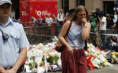 A woman cries after laying a flower at a makeshift memorial in Sydney, Australia Tuesday, Dec. 16, 2014 near where three people died in a siege. (photo credit: AP Photo/Nick Perry)