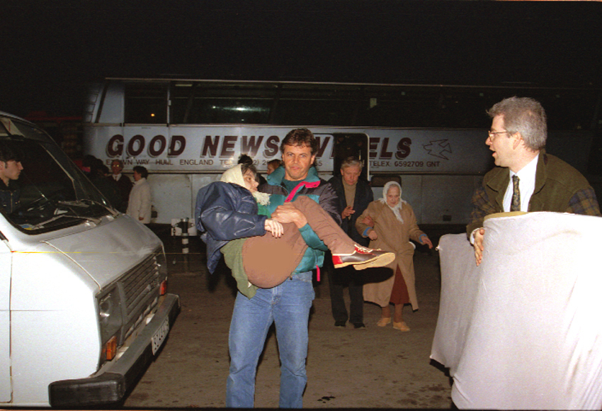 Former International Christian Embassy international director Michael Utterback assists a disabled Russian Jew from a bus onto a plane for the flight to Israel. It is a literal fulfillment of Isaiah 49:22-23, which speaks of God using gentiles to bring the sons and daughters of Israel home 'in their arms' in 1992. (courtesy)