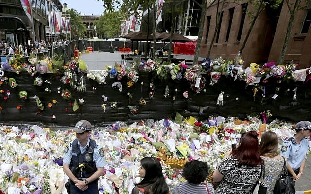 Police stand watch over flower tributes to the shooting victims on the footpath outside the the cordoned off area outside the Lindt cafe in the central business district of Sydney, Australia, Wednesday, Dec. 17, 2014. (photo credit: AP/Rob Griffith)