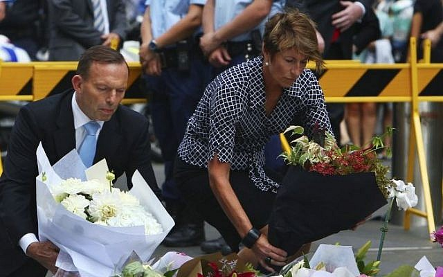 Australian Prime Minister Tony Abbott and his wife Margie pay their respect to the victims of the siege in Martin Place in Sydney central business district, Australia. Tuesday, Dec. 16, 2014.  (Photo credit: Steve Christo)