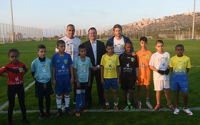 British Ambassador to Israel Matthew Gould (center, back) is pictured with Maccabi Tel Aviv soccer players Maharan Radi (left) and Sheran Yeini (right) and Jewish and Arab children from the north of Israel. (photo courtesy: Ben Kelmar/British Consulate)