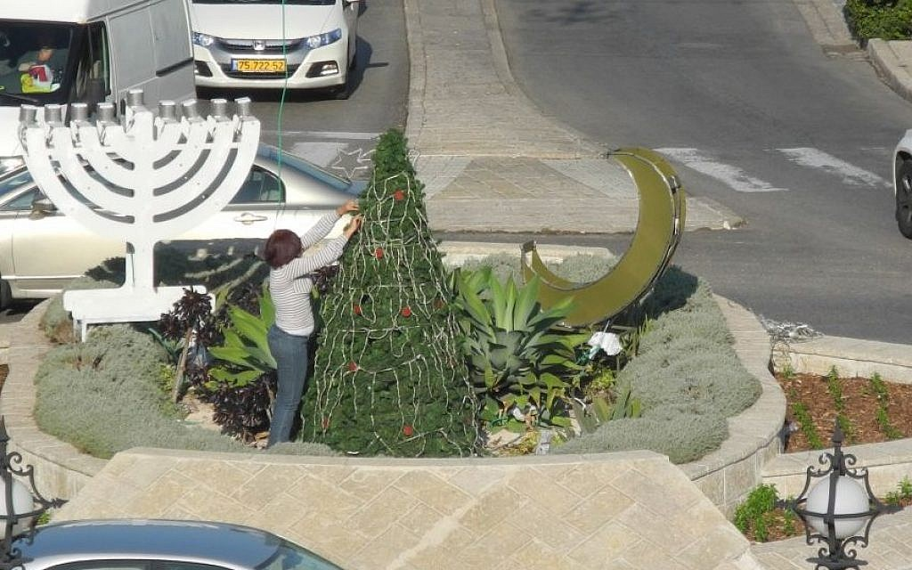 A worker puts the finishing touches on a display of a Christmas tree, a crescent, and a menorah at the main traffic circle in front of the Bahai Gardens in Haifa for the Festival of Festivals, December 2014. (photo credit: Melanie Lidman/Times of Israel)