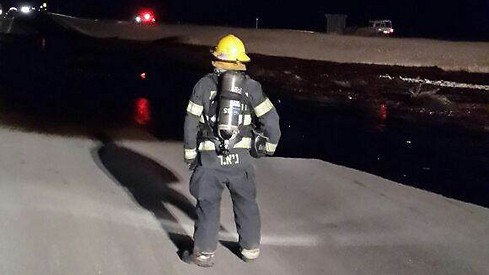 "A firefighter looks following a major oil spill north of Eilat leading to ""extensive contamination"" as a result of a damage to the Trans-Israel pipeline December 4, 2014. (photo credit: Courtesy Police Spokesman's Unit)"