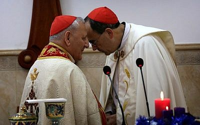 Patriarch of the Chaldean Church, Louis Raphael Sako (L) speaks with Archbishop of Lyon Monseigneur Philippe Barbarin during mass at Saint Marilia church in Erbil, attended by Iraqis who fled the violence in the northern city of Mosul after Islamic State group militants took control of the area, in the capital of the autonomous Kurdish region of northern Iraq, on December 6, 2014. (photo credit: AFP PHOTO / SAFIN HAMED)