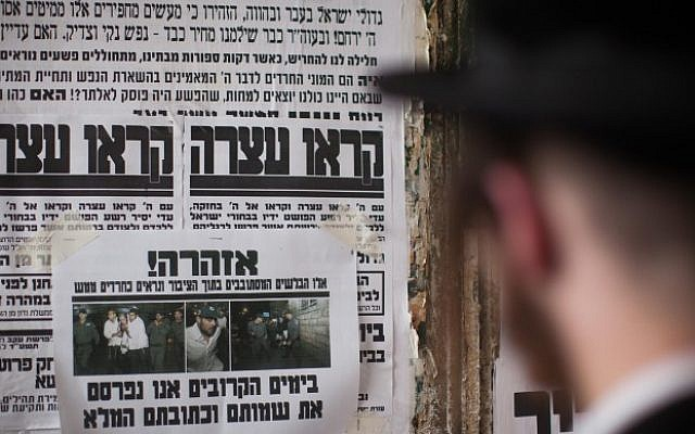 "Illustrative photo of an Ultra Orthodox Jewish man reading a ""Pashkvil""-- an information poster -- in the ultra-Orthodox Jerusalem neighborhood of Meah Shearim, August 19, 2014. (Photo credit: Yonatan Sindel/Flash90)"
