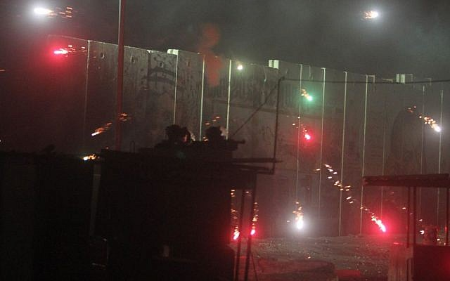 Illustrative photo of Israeli border police and soldiers clashing with Palestinians shooting fireworks at the Qalandiya checkpoint on July 24, 2014. (Issam Rimawi/FLASH90)