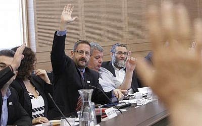 Dov Lipman of Yesh Atid votes at a Knesset Finance Committee meeting, September 2014 (Photo credit: Miriam Alster/Flash90)