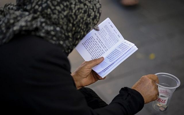 Illustrative photo of a Jewish woman seen with a prayer book (Photo credit: Mendy Hechtman/FLASH90)