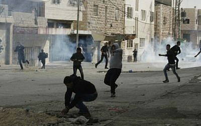 Palestinian rioters throw stones during clashes with Israeli soldiers in the West bank town of Hebron, on November 21, 2014. (Photo credit: Ibrahim Hmouz/Flash90)