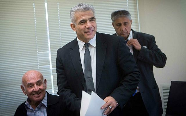 Finance Minister Yair Lapid (center) and Science Minister Yaakov Peri (left) at a Yesh Atid faction meeting in the Knesset, December 1, 2014. (Miriam Alster/Flash90)