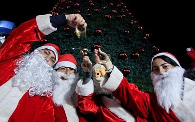 Palestinians decorate a Christmas tree in the West Bank city of Ramallah, as preparations for Christmas celebrations continue, December 7, 2014. (Photo credit: STR/Flash90)