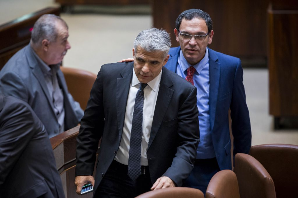 Yair Lapid, center, with outgoing education minister Shai Piron (right) during a vote on a bill to dissolve the Knesset on December 8, 2014 (photo credit: Yonatan Sindel/Flash90)