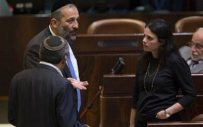 Shas party Aryeh Deri speaks with Jewish Home MK Ayelet Shaked during a vote on a bill to dissolve the Knesset, on December 8, 2014. (Photo credit: Yonatan Sindel/Flash90)